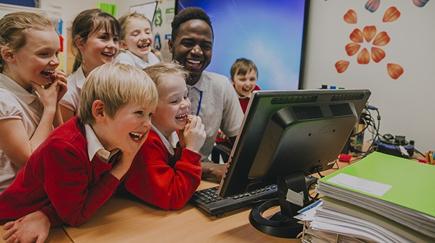 Primary school students crowded round a computer