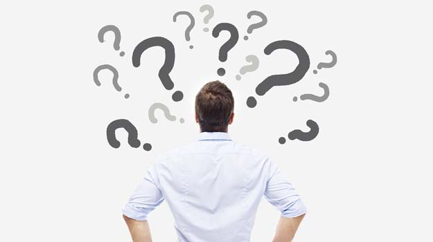 Man with question marks around his head.